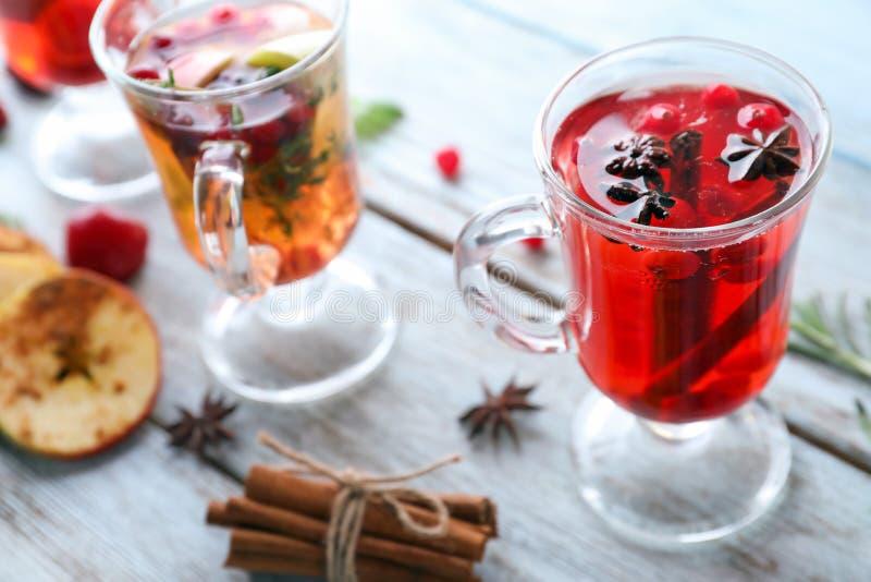 鲜美饮料用蔓越桔和香料在玻璃杯子在桌上 库存图片