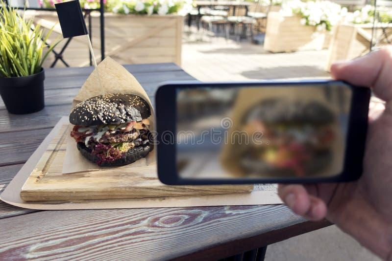 鲜美黑汉堡食物摄影在户外咖啡馆的 人韩 图库摄影
