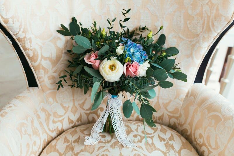 鲜花婚礼花束站立在扶手椅子的新娘的 免版税库存照片