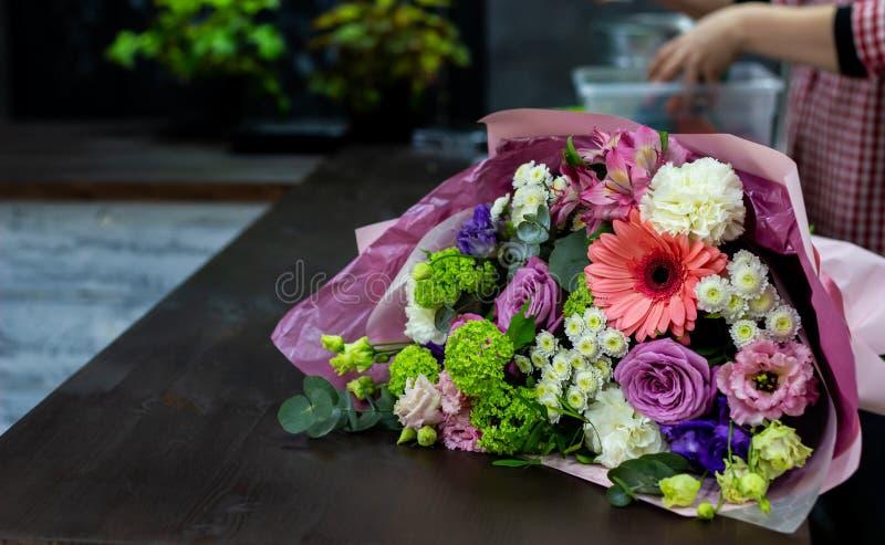 鲜花明亮的花束在一张棕色木桌上的 库存照片