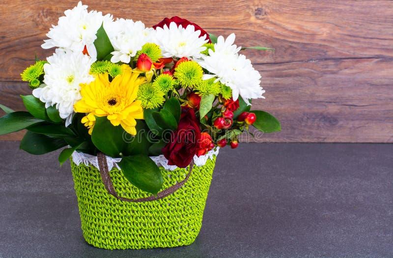 鲜花的植物布置在绿色柳条筐o的 免版税库存照片