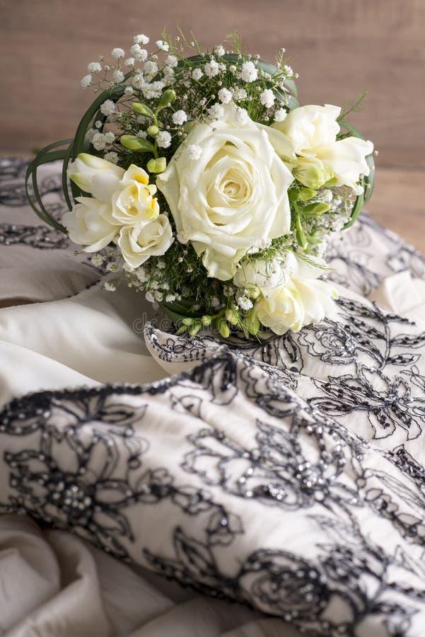 鲜花花束在婚礼服顶部的 免版税图库摄影