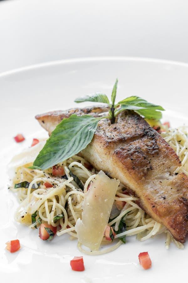 鲜鱼去骨切片混杂的菜和巴马干酪意粉过去 库存图片