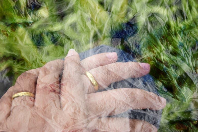 鲜绿色的背景一个人以妇女举行手和穿戴g 免版税库存图片