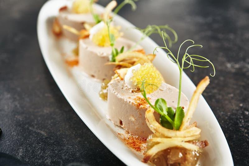 鳕鱼肝脏、葱和酥脆芯片奶油甜点  库存图片