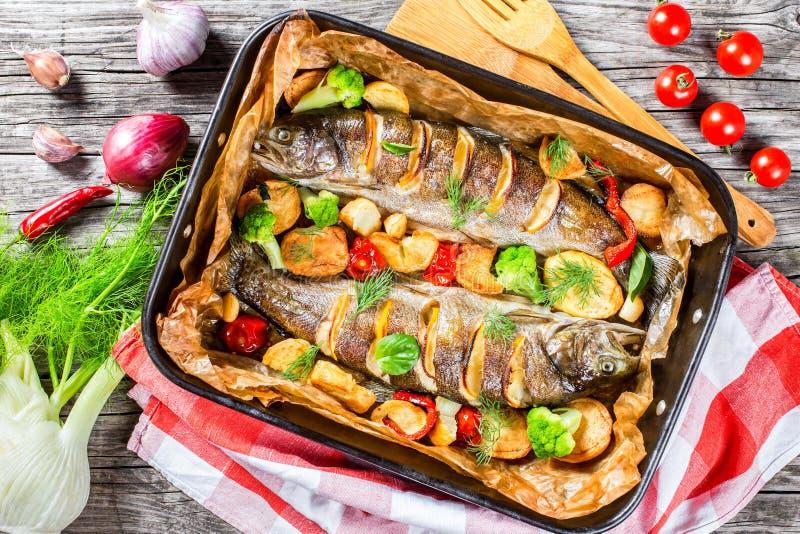 鳟鱼鱼烘烤了用土豆,硬花甘蓝,柠檬,蕃茄 免版税图库摄影