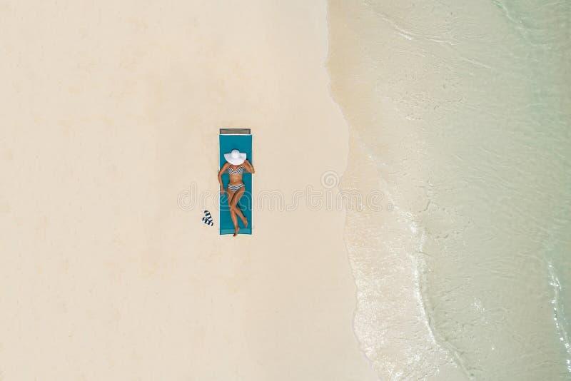 鸟瞰图亭亭玉立的妇女晒日光浴的说谎在一张海滩睡椅在马尔代夫 与女孩,美丽的波浪的夏天海景,五颜六色 免版税图库摄影