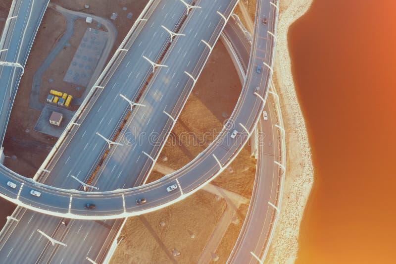 鸟瞰图在一个公路交叉点的高速公路圈在日落的晚上 免版税库存图片