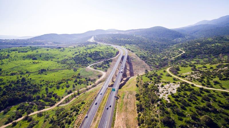 鸟瞰图射击了飞行在青山领域,提出高速公路路和现代桥梁 免版税库存图片