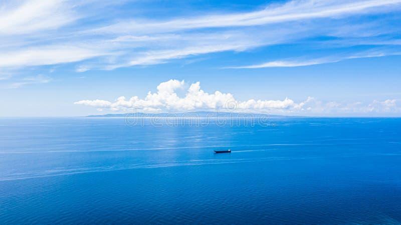 鸟瞰图蓝色海水表面和天空蔚蓝,在天空蔚蓝的美丽的白色云彩在有阳光反射的,奥斯洛斯风平浪静 库存图片