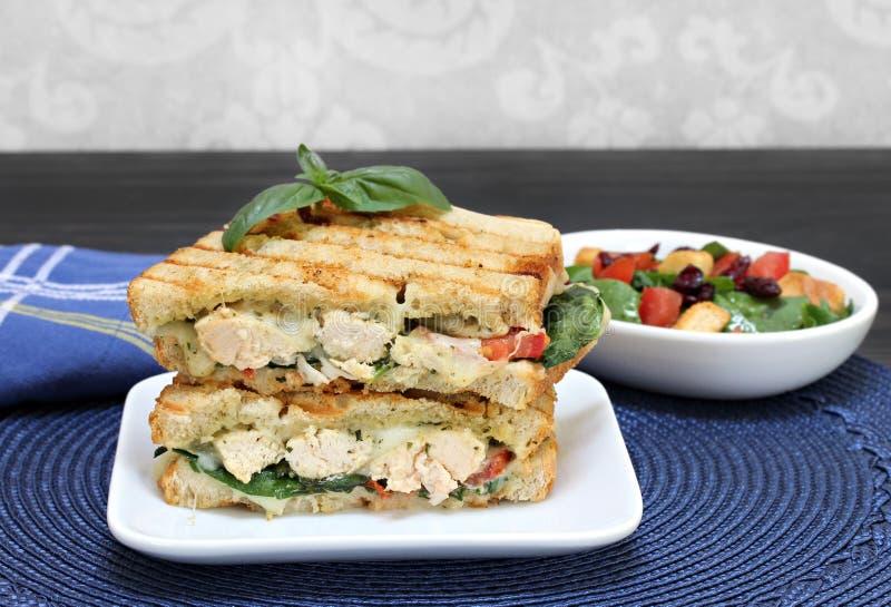 鸡、蓬蒿、菠菜、蕃茄、pesto和乳酪panini 免版税库存图片