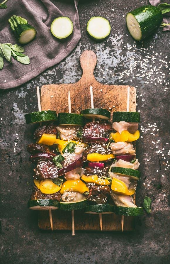 鸡和牛肉肉各种各样的肉串在切板的在与菜的黑暗的背景 免版税图库摄影