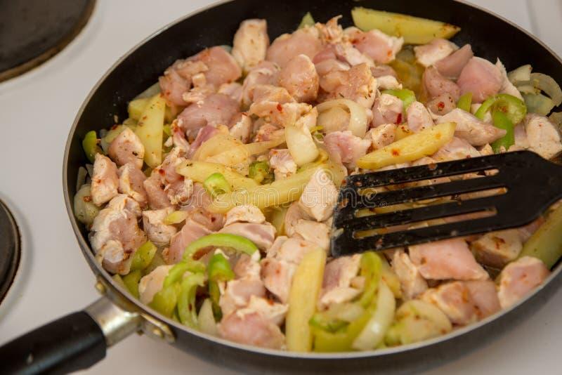 鸡在一个电火炉的一个煎锅油煎 E 库存照片