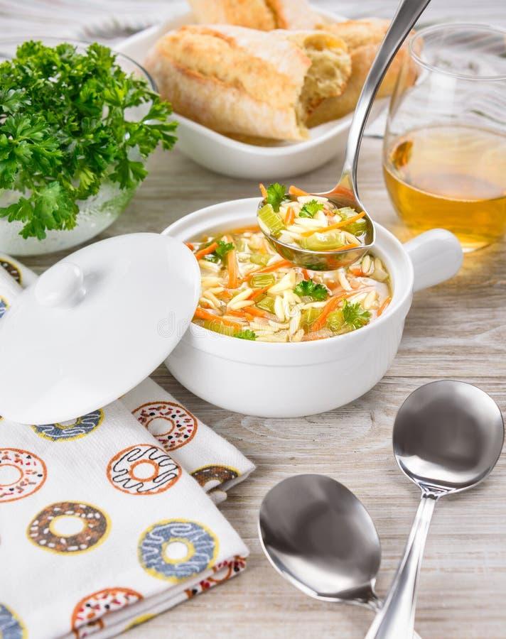 鸡在白色缸的orzo汤在木背景 与orzo面团的意大利汤 杓子 面包 玻璃酒 免版税库存图片