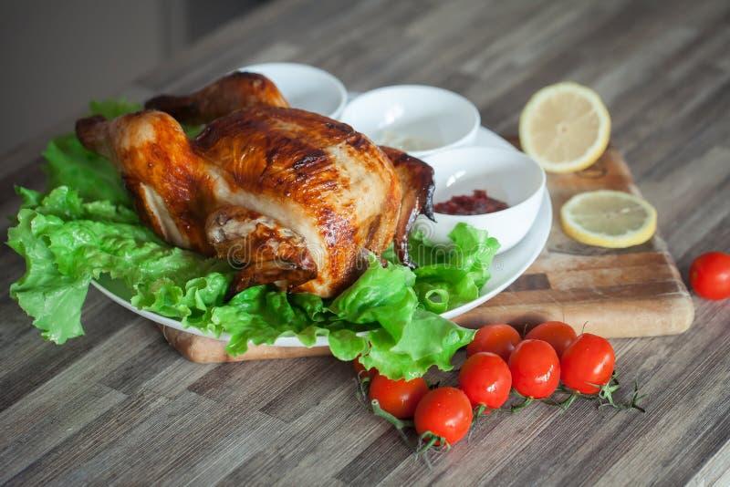 鸡在绿色莴苣叶子的一个格栅用西红柿 库存照片