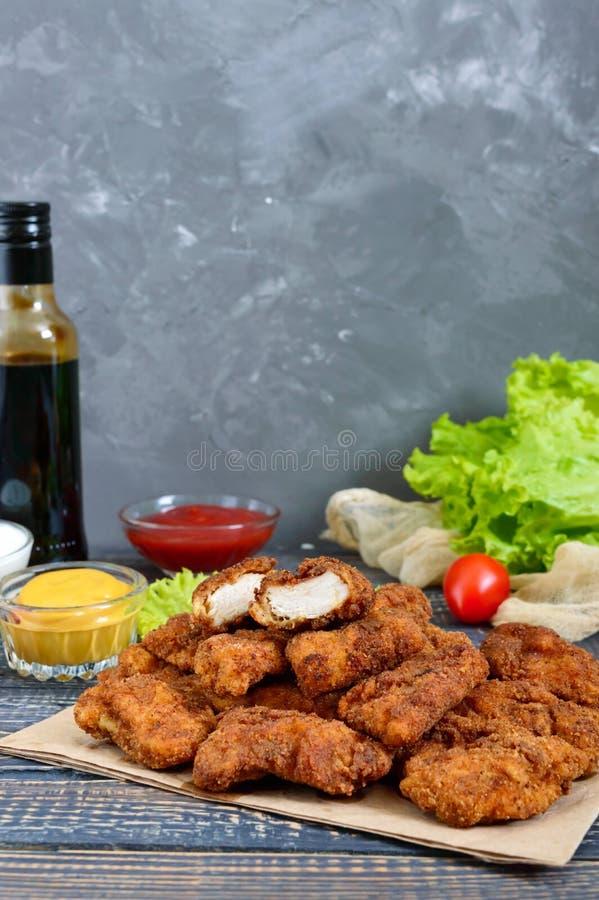 鸡块 油炸酥脆肉片断,在用不同的调味汁的纸在一张木桌上 库存照片