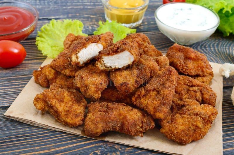 鸡块 油炸酥脆肉片断,在用不同的调味汁的纸在一张木桌上 免版税库存图片