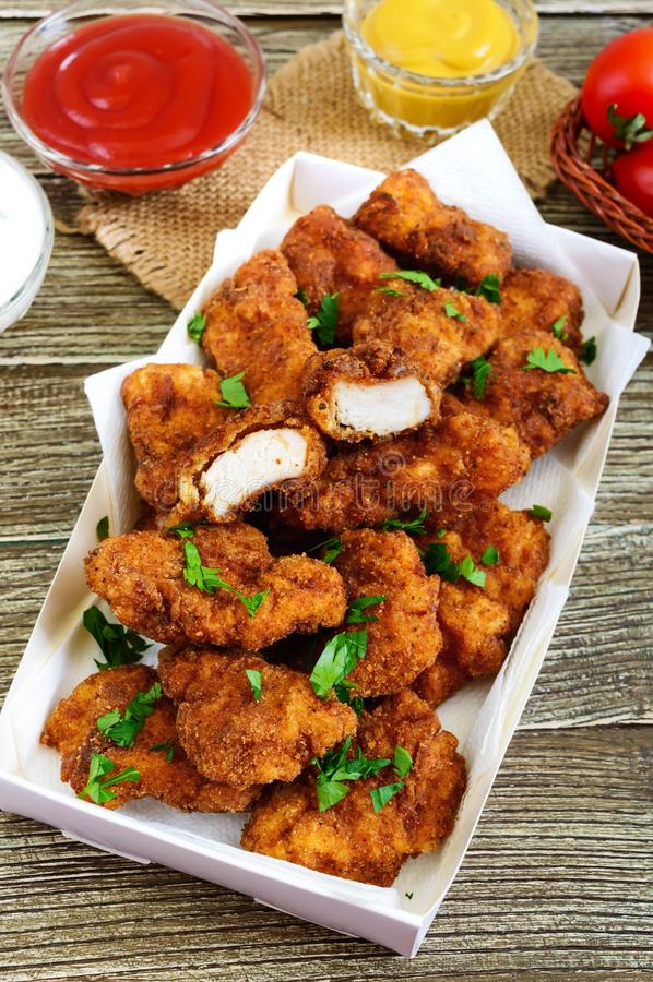 鸡块 油炸酥脆肉片断,用不同的调味汁 免版税库存照片