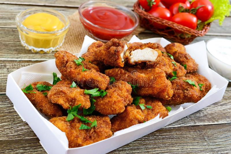 鸡块 油炸酥脆肉片断,用在一张木桌上的不同的调味汁 免版税库存照片