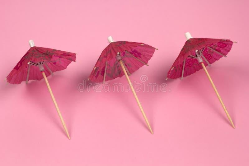 鸡尾酒伞样式桃红色背景 免版税库存照片