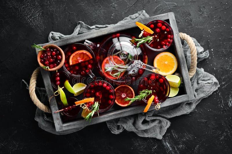 鸡尾酒和酒 蔓越莓,柠檬,迷迭香 黑色背景中 顶视图 库存照片
