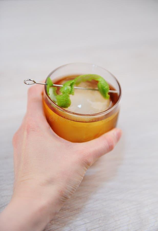 鸡尾酒威士忌酒与石灰的兰姆酒可乐和冰一个整个圆的片断  在手中轻的木表面上 库存图片