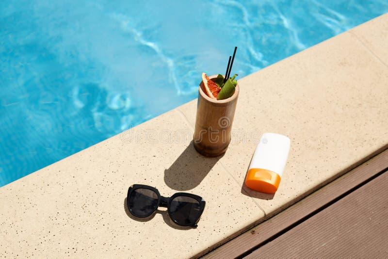 鸡尾酒平的位置在木容器、黑时兴的太阳镜和太阳保护奶油的在白色瓶,组成 库存照片