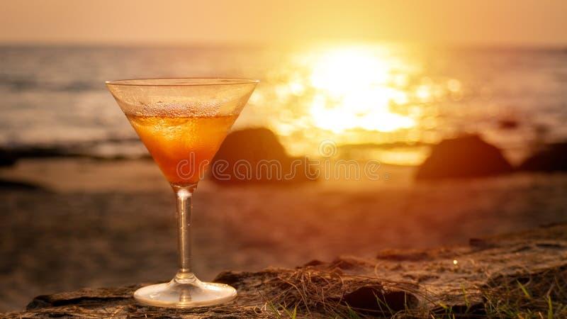 鸡尾酒杯有海在背景的海滩视图在日落时间 图库摄影