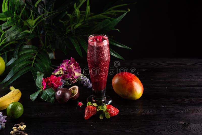 鸡尾酒用果子和莓果在一块高玻璃在黑暗的背景 免版税库存照片
