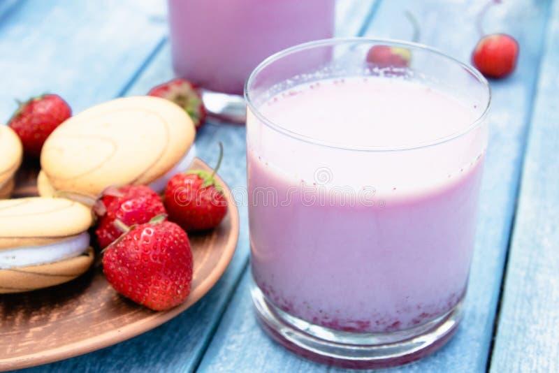 鸡尾酒用牛奶和莓果在玻璃棍打以蓝色委员会为背景 图库摄影