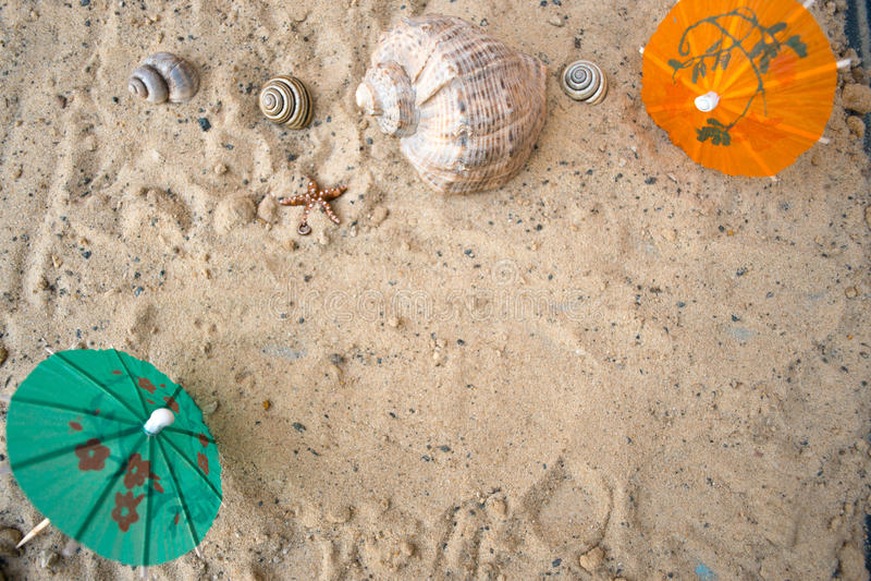 鸡尾酒的伞在含沙夏天背景 库存图片