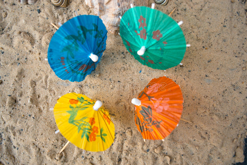鸡尾酒的伞在含沙夏天背景 免版税库存图片
