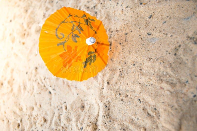 鸡尾酒的伞在含沙夏天背景 免版税库存照片