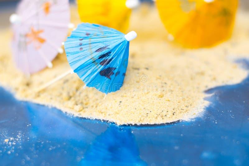 鸡尾酒的伞在含沙夏天背景 库存照片