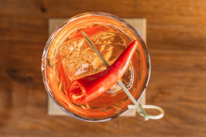 鸡尾酒顶视图服务用在玻璃的红色辣椒与在木桌上的冰 库存图片