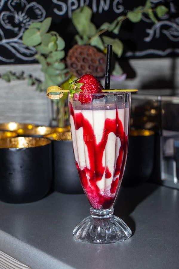 鸡尾酒鸡尾酒用在一块美丽的雕琢平面的玻璃的草莓酱在酒吧柜台 库存照片