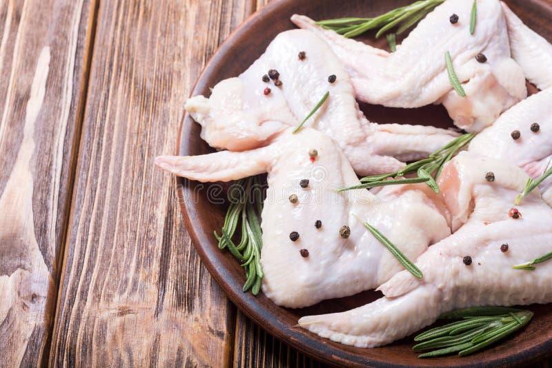 鸡未加工的翼用迷迭香、大蒜、胡椒和盐 免版税库存图片