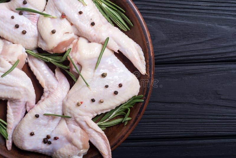鸡未加工的翼用迷迭香、大蒜、胡椒和盐 图库摄影