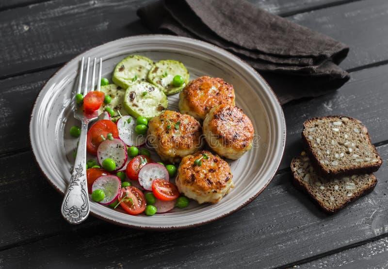 鸡炸肉排和新鲜蔬菜沙拉在陶瓷板材在黑暗的木背景 库存图片