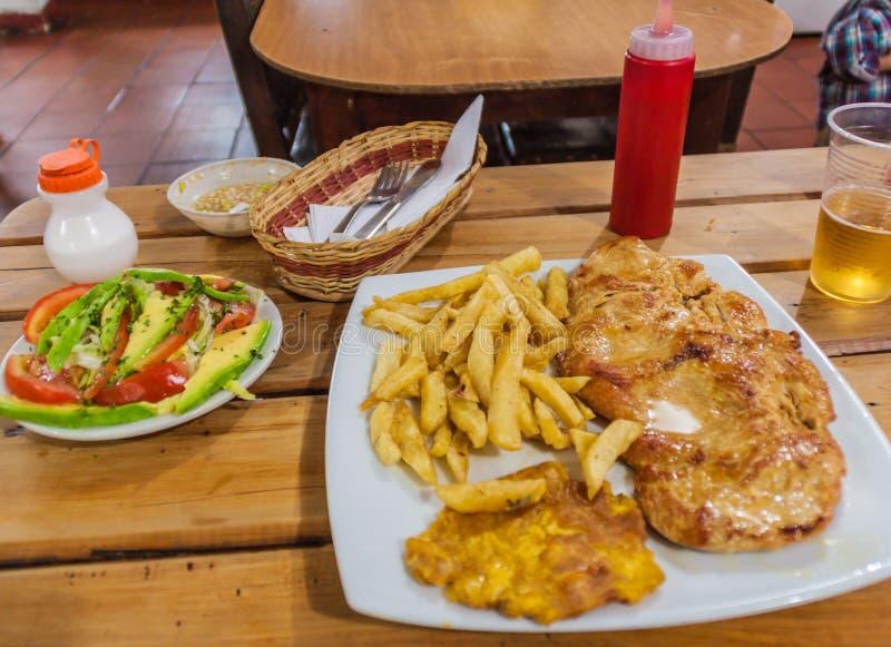 鸡牛排在一家餐馆在哥伦比亚 陪同由薯条、patacon和sala 库存图片