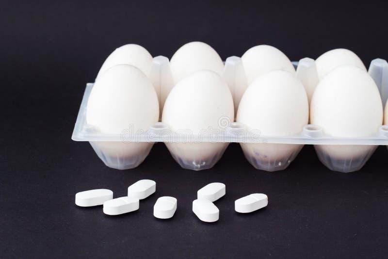 鸡盘子怂恿在黑背景和在谎言药片抗生素,特写镜头旁边 免版税库存照片