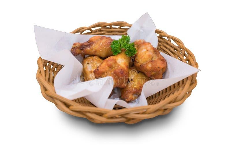 鸡翅和鼓槌烤肉支持与油在柳条筐的吸收体纸 库存照片