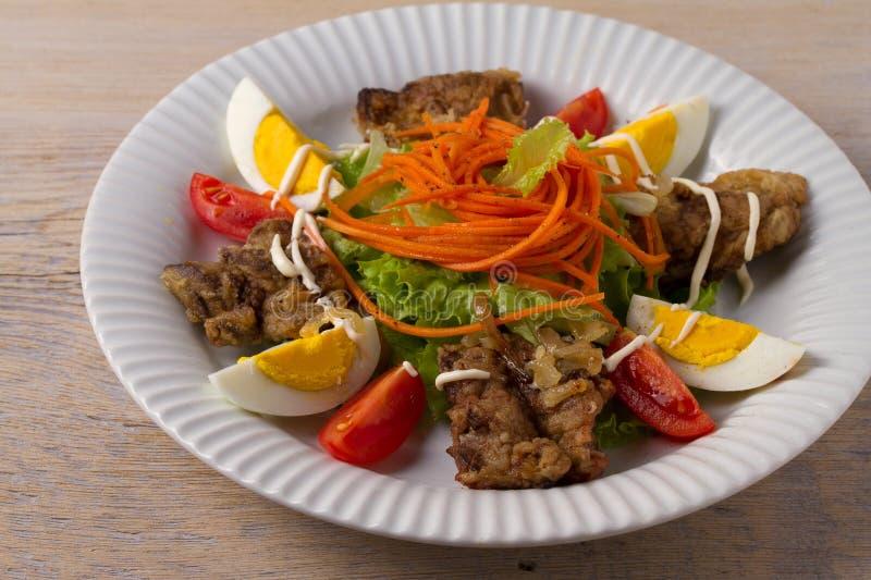 鸡肝、红萝卜、鸡蛋、蕃茄、莴苣和油煎的葱沙拉 肝脏和菜 库存图片