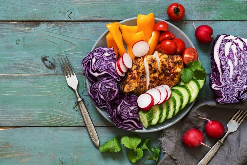 鸡胸脯烘烤用香料服务与新鲜蔬菜,红叶卷心菜,萝卜,黄瓜,甜椒,在gre的蕃茄 免版税库存照片