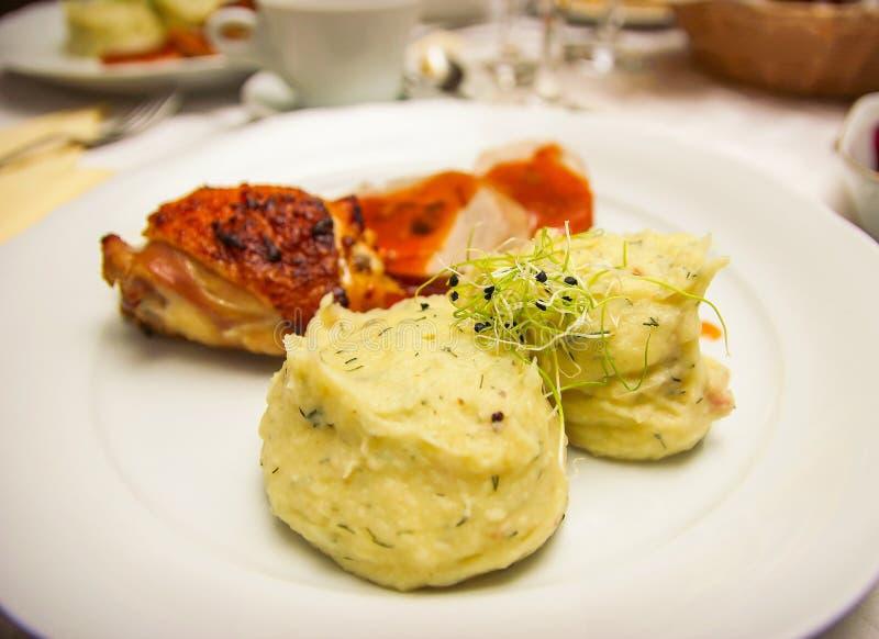 鸡胸脯牛排用混杂的mushed土豆和香料在一块白色板材 免版税库存照片