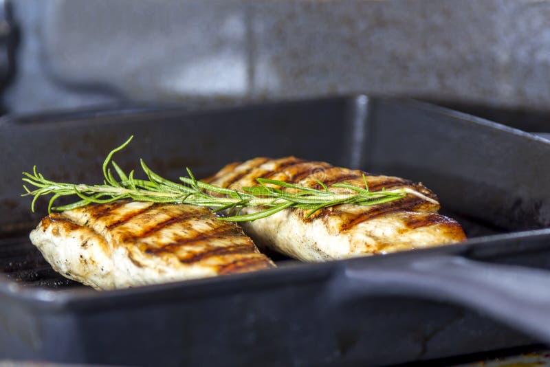 鸡胸脯用在平底锅的迷迭香 库存照片