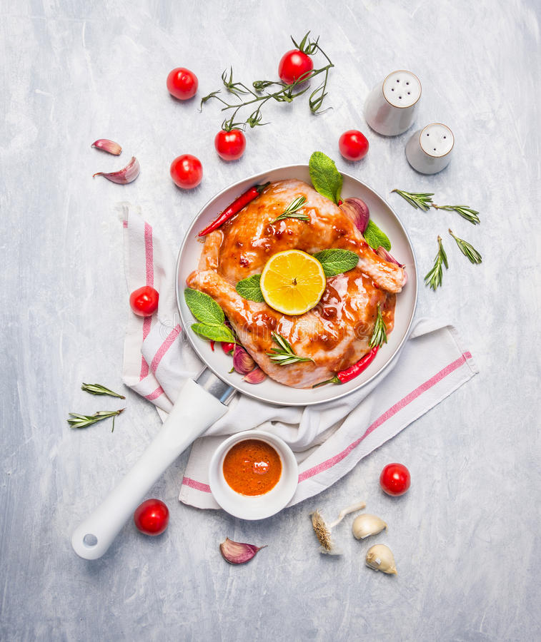 鸡腿用红色辣椒卤汁、草本和香料在白色平底锅在蓝色木背景 图库摄影
