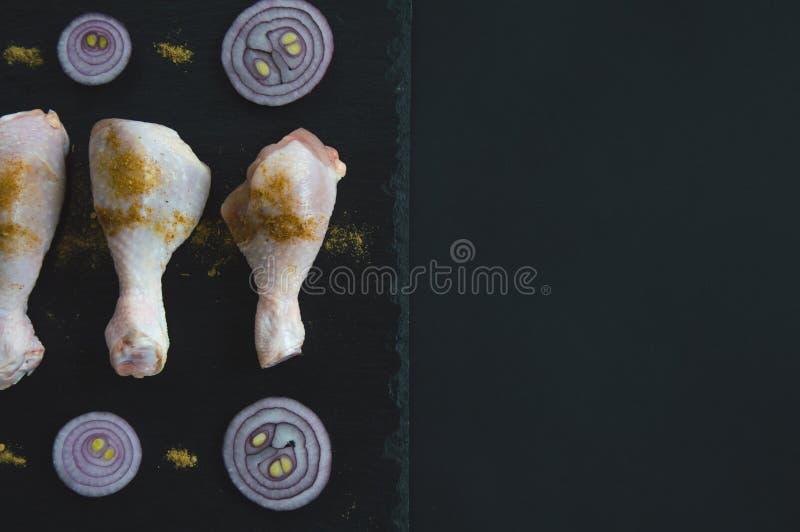 鸡腿用香料和红洋葱在黑人石委员会说谎 烹调鸡腿 图库摄影