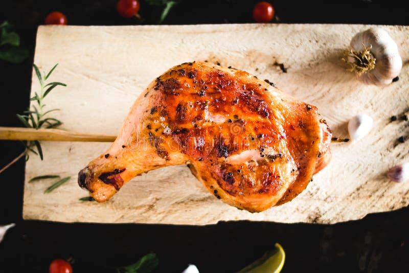 鸡臀部在木砧板烤安置的大蒜胡椒 免版税库存照片