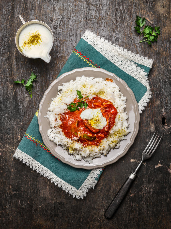鸡蕃茄在木背景的炖煮的食物用印度大米用在板材的酸奶调味汁和叉子 库存照片